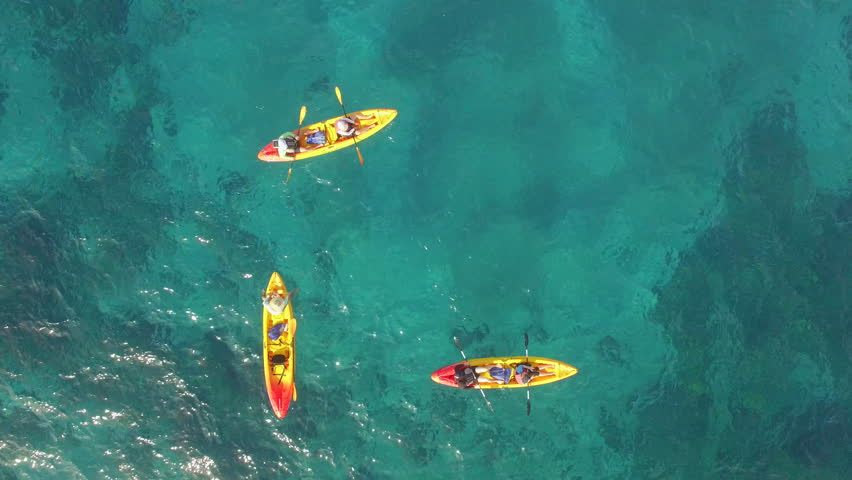 Top View of Kayaks kayaking and enjoying the tropical crystal clear turquoise blue waters in paradise. Snorkeling and fishing.