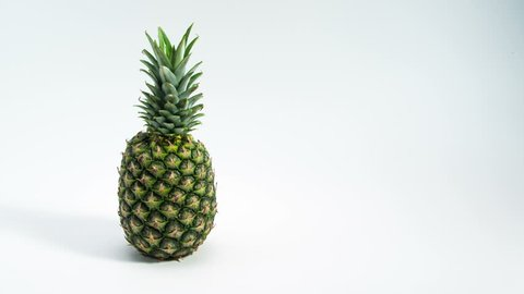 Pineapple appearing on white table with empty space for your text. 4K Stop motion food animation.