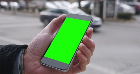 A man holding a green screen smartphone in a city. Green screen with optional corner pin points for advanced tracking and screen replacement.