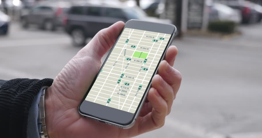 A man uses his smartphone to observe ride sharing traffic patterns on an interactive map in a city.  	 | Shutterstock HD Video #23738827