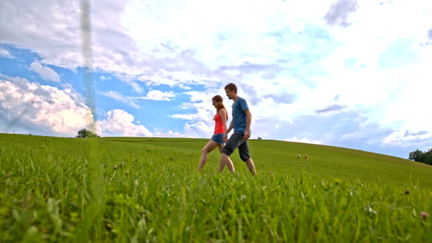 Warm summer stroll on green lawn.Low angle wide shot of two person holding hands in focus and walk from right side of shoot frame to left side.