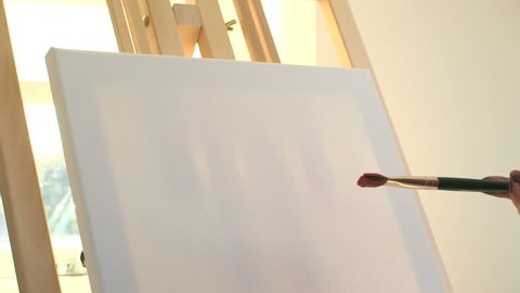 CU. Artist getting ready to paint on a empty canvas. Bournemouth, UK.