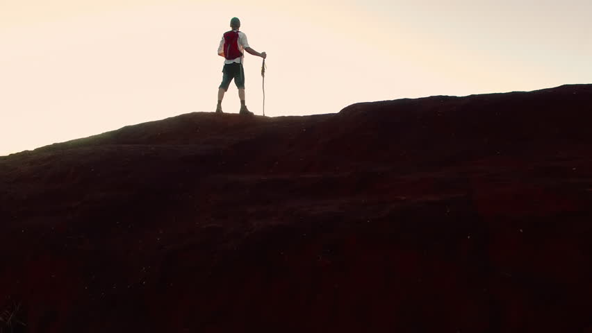 4k drone footage of hiker walking and drinking water with red backpack in desert mountain terrain at sunset.  | Shutterstock HD Video #23794951