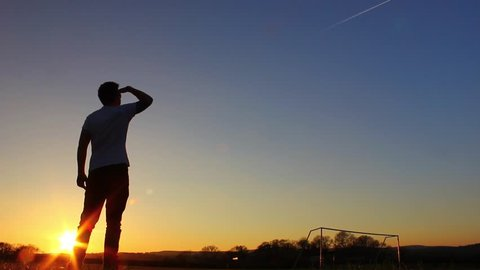 Silhouette of man looking up at plane trails in the sky, sunset