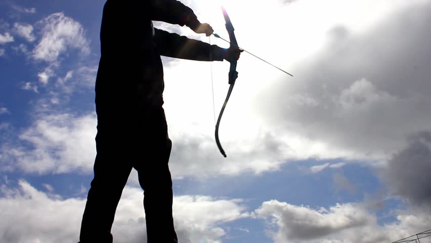 Silhouette of man using bow and arrow