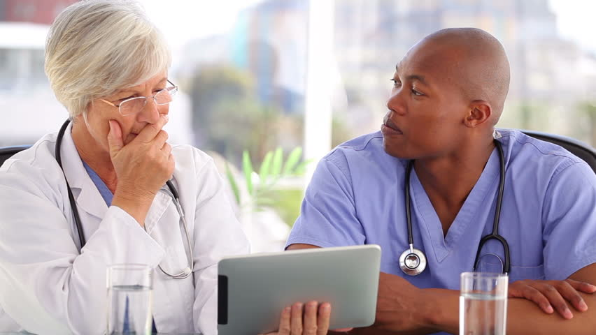 Mature doctor talking with a nurse in front of a touchscreen in a bright office