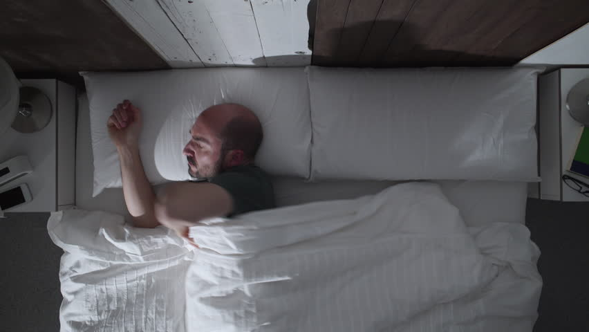 Young adult man can't sleep at night because of his noisy neighbors. He turns in bed, wakes up and hits the wall.