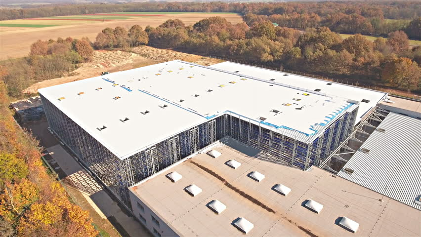 Drone ascending over warehouse zooming out 4K. Aerial ascend away from building and uncovering more forest around the building. Sunny fall time.