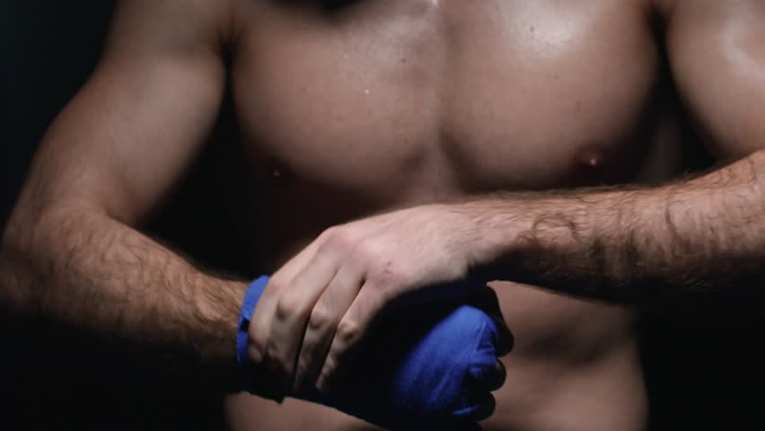 Closeup of muscular shirtless fighter rubbing hand in protective MMA wrap and then punching fist into palm