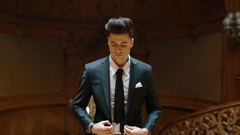 Portrait of young caucasian man in black suit indoor. Model buttons his jacket.