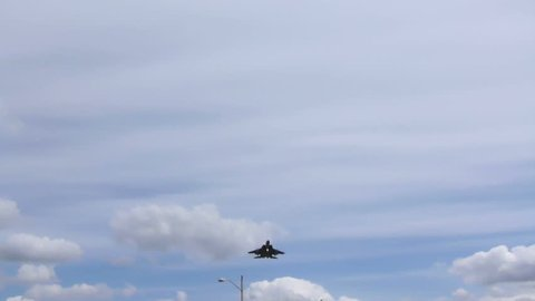 F15 fighter jet flying overhead on cloudy day.