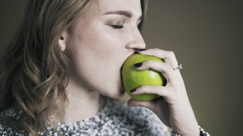 Close up portrait of young girl biting and eating tasty green apple and looking at camera. Locked down real time shot.