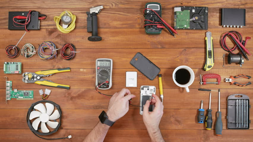 Man repairing a mobile phone. Checks parts inside the device. Wooden table top view. | Shutterstock HD Video #23904124