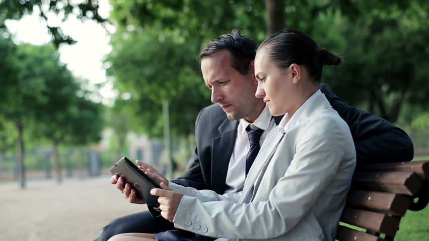 Business couple with tablet computer in the park, dolly shot  | Shutterstock HD Video #2392832