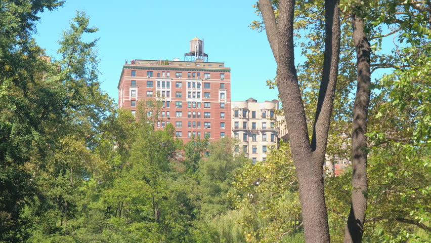 CLOSE UP: Beautiful red brick luxury apartment building and lowrise block of flats in residential area, Manhattan Upper West Side, overlooking green trees in breathtaking Central park in New York City