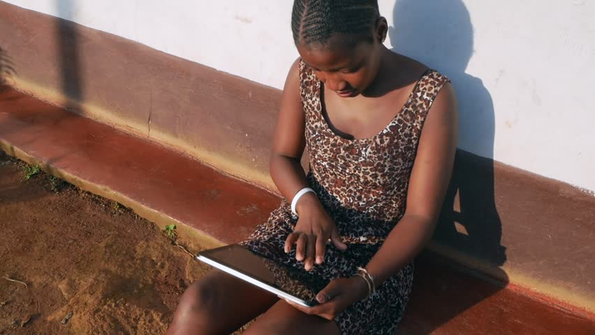 A rural South African black woman working or texting using computer tablet in village | Shutterstock HD Video #23934511