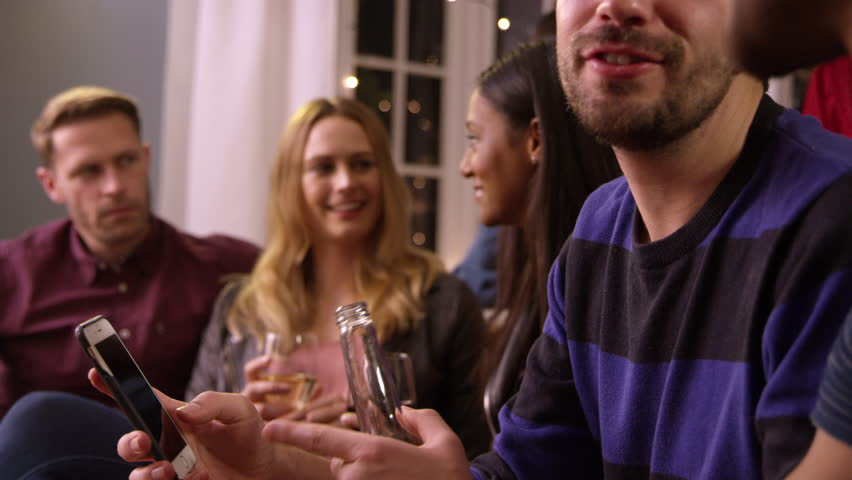 Man Checking Mobile Phone At Party With Friends #23955451