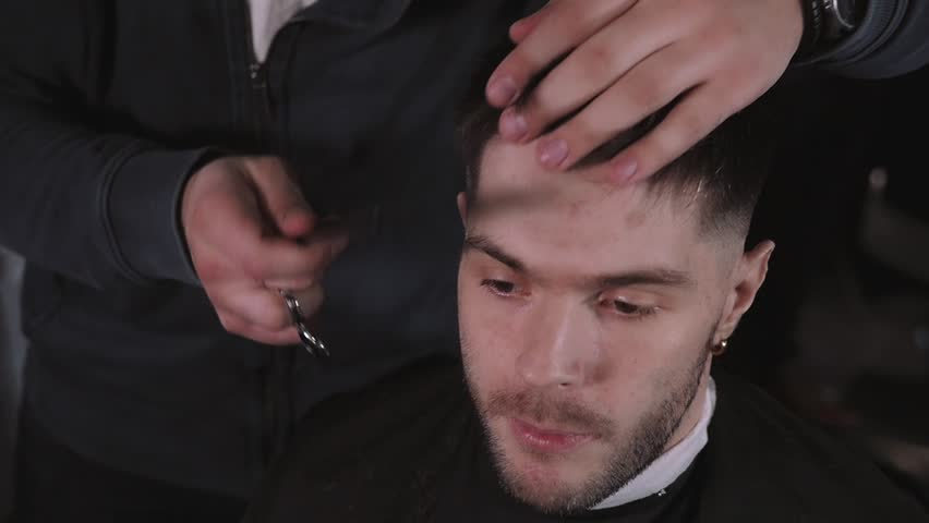 Making haircut look perfect. Young bearded man getting haircut by  hairdresser while sitting in chair
