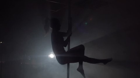 Young woman exercising pole dance fitness, slow motion. Silhouette.