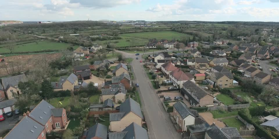 Aerial view of UK middle class houses in small village or town in the countryside. Top view above houses surrounded by green lawns and farmland.