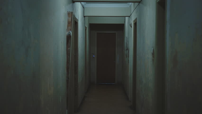 Walking inside a long dark hallway of an old apartment building.