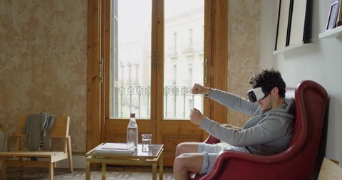 Man wearing virtual reality headset playing game 360 video immersive concept at home