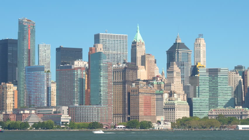 Iconic view of Lower Manhattan financial district skyline from the vantage point on Hudson River. Ferry transferring people, tourists traveling on yacht overlooking majestic contemporary skyscrapers | Shutterstock HD Video #24004021