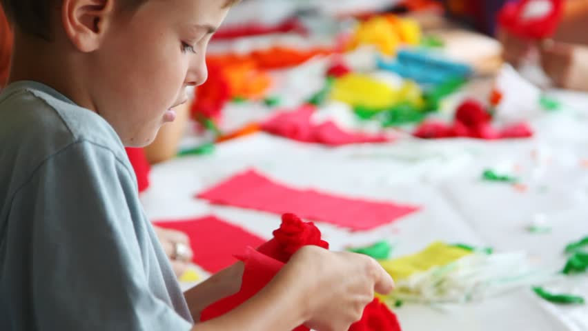 Boy together with other children makes flower of color paper | Shutterstock HD Video #2401661