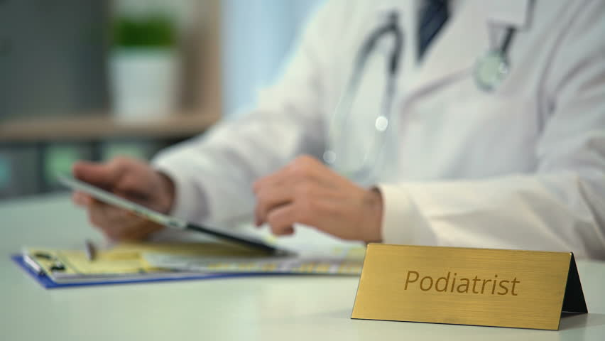Podiatrist viewing patient's x-rays on tablet, modern technologies in medicine