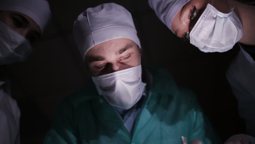 Doctors surgeons operate patient in operating theater. Surgical team performing operation in hospital operating room. Surgery on specialized clinic.