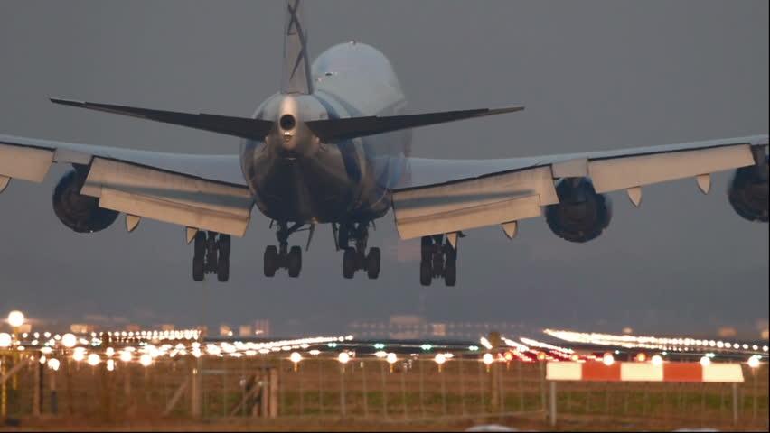 Big jumbojet cargo airplane landing at the runway.