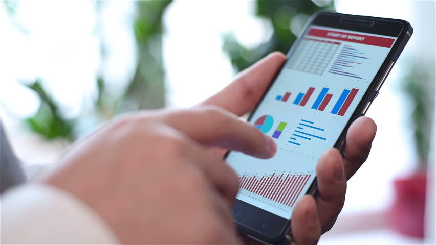 Hand Holding Mobile Phone With Stock Graph And Financial Statistics On Screen | Shutterstock HD Video #24033871