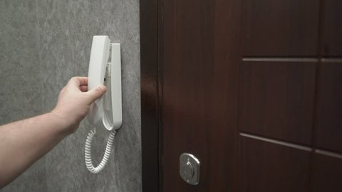 Person holding handset of intercom system installed on a wall in the apartment answering a call