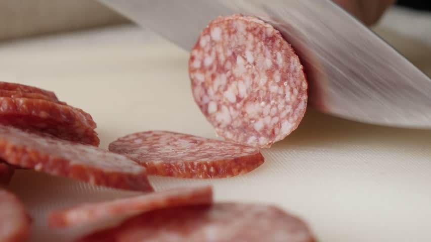 Using knife for smaller pieces cut of pork salami 4K 2160p 30fps UltraHD footage - Cutting cured sausage of air-dried meat close-up 3840X2160 UHD video | Shutterstock HD Video #24045562