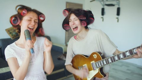 Two funny girls singing with comb and playing electric guitar, dancing and singing.