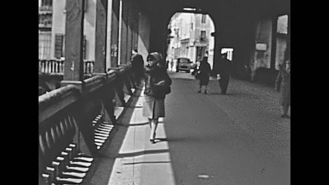 Bassano del Grappa, Vicenza, Italy - circa 1960: woman walking under the historical old Alpini bridge of Bassano del Grappa in Italy. Bridge was build in 1209 and restored in time. Historical footage