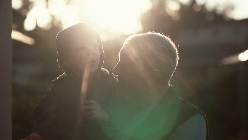 CLose-up of grandfather holding grandson on hands, hugs and kiss boy on cheek. Old man standing outdoor in sunlight. 4K