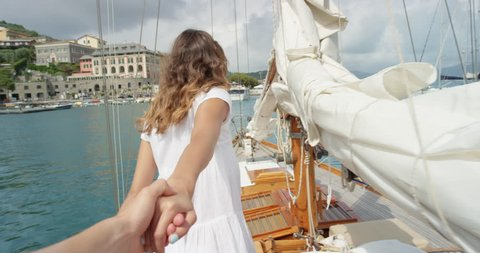 Beautiful couple holding hands woman leading boyfriend onto luxury wooden yacht sailboat POV travel concept