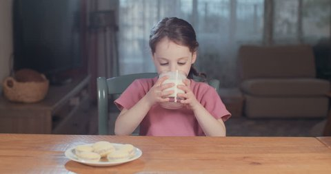 Girl drinking a glass of milk with cookies