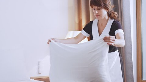 Middle-aged Caucasian female chambermaid in unifrom making bead and beating pillows in slowmotion
