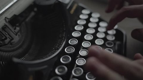 man typing on retro typewriter close up.