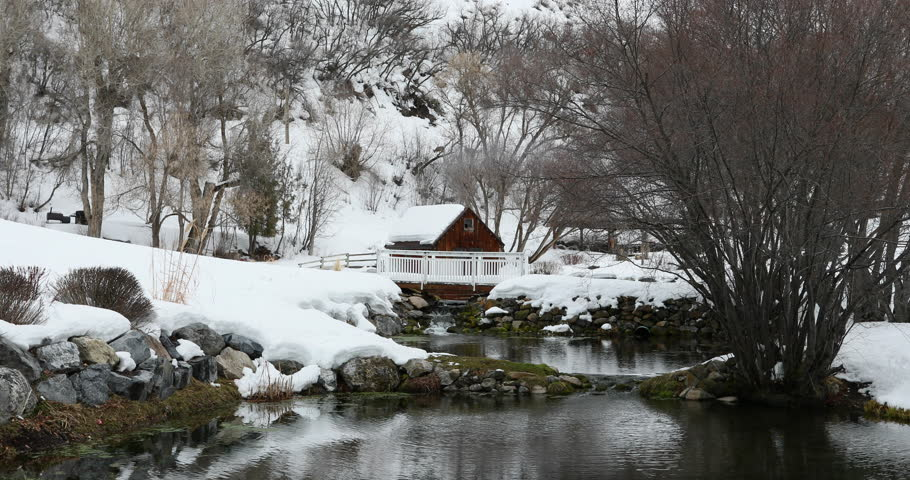 UTAH COUNTY, UTAH - FEB 2017: Winter mountain valley cabin on stream pond. Winter snow on landscape. Pond, stream and cabin. Mountain valley landscape. Cold season weather. Nature and environment.