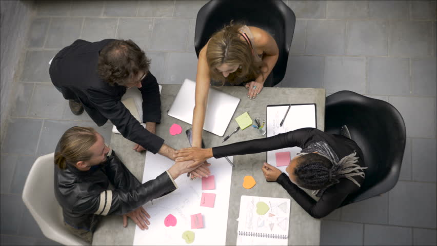 A group of millennial collaborators celebrate teamwork with fist bumps and a team cheer | Shutterstock HD Video #24120901