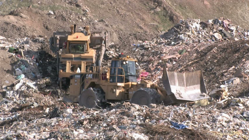 SALT LAKE CITY - CIRCA 2008: Bull dozers moving garbage and trash around in garbage dump circa 2008 in Salt Lake City, Utah.