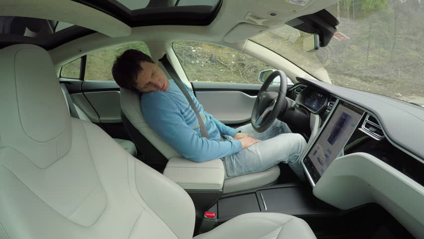 AUTONOMOUS TESLA CAR, FEBRUARY 2016: Male driver sleeping behind the self-driving steering wheel of a autonomous electric Tesla car. Man fell deeply asleep while driving along the countryside road #24134221