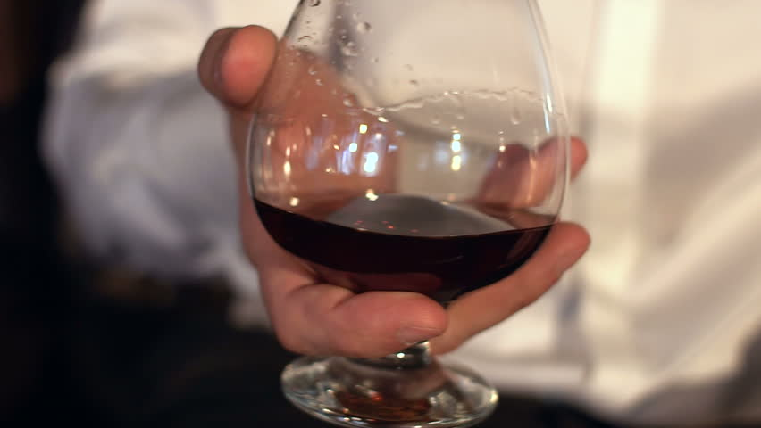 Man stir slowly cognac in the glass, slow motion.Glass of whiskey in male hands.