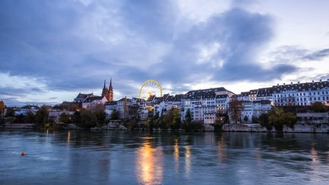 BASEL, SWITZERLAND – November 5, 2016: River with city skyline and ferris wheel in the cloudy evening zoom in timelapse Basel Rhine with city in the evening