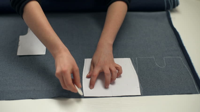Hands of seamstress drawing the lines on the tissue with a piece of soap | Shutterstock HD Video #24173401