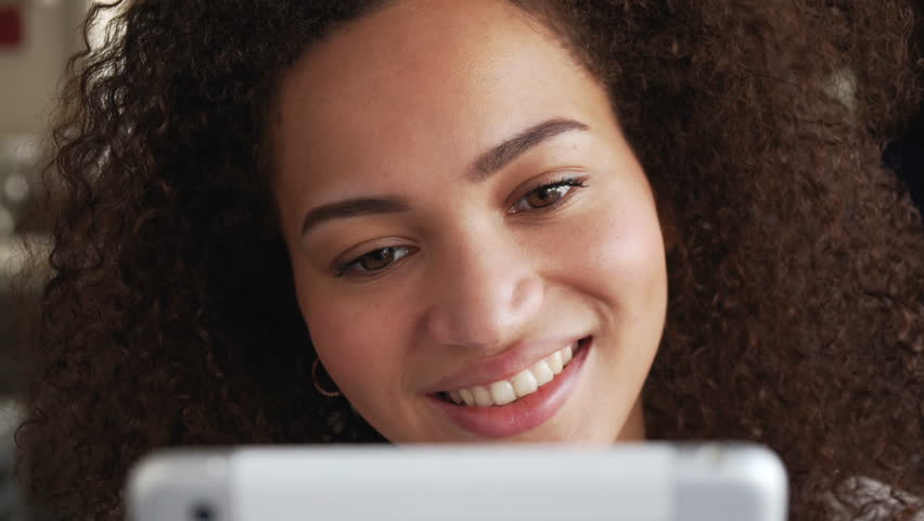 Smiling afro american woman with curly hair overlook social young happy smiling afro american woman with curly hair overlook social network account and photos urmus Image collections