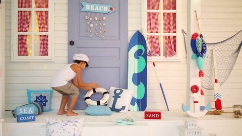 Boy takes a lifeline and sits next to the door in a room with sea decoration